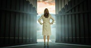 Sammansatt bild av affärskvinnan som är stående tillbaka till kameran 3d Royaltyfria Foton