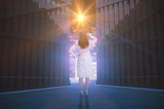Sammansatt bild av affärskvinnan som är stående tillbaka till kameran med handen på huvudet 3d Arkivfoton