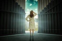 Sammansatt bild av affärskvinnan som är stående tillbaka till kameran med handen på huvudet 3d Royaltyfri Foto
