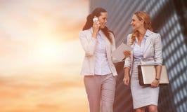 Sammansatt bild av affärskvinnor som använder mobiltelefonen, medan gå royaltyfri fotografi