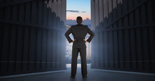 Sammansatt bild av affärsmannen som är stående tillbaka till kameran med händer på höften 3d Arkivbild