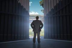 Sammansatt bild av affärsmannen som är stående tillbaka till kameran med händer på höften 3d Arkivfoton