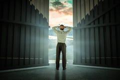Sammansatt bild av affärsmannen som är stående tillbaka till kameran med händer på huvudet 3d Royaltyfri Bild