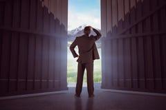 Sammansatt bild av affärsmannen som är stående tillbaka till kameran med handen på huvudet 3d Royaltyfri Bild