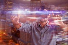Sammansatt bild av affärsmannen som gör en gest, medan genom att använda virtuell verklighetsimulatorn royaltyfri bild