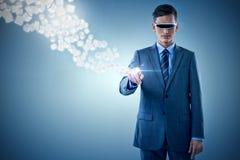 Sammansatt bild av affärsmannen som pekar, medan genom att använda virtuell verklighetexponeringsglas 3d Royaltyfri Bild
