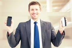 Sammansatt bild av affärsmannen som rymmer två smarta telefoner Arkivbilder