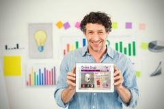 Sammansatt bild av affärsmannen som visar den digitala minnestavlan med den tomma skärmen i idérikt kontor Royaltyfria Foton