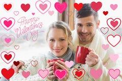 Sammansatt bild av att älska par i vinterkläder med kaffekoppar mot fönster Arkivbild