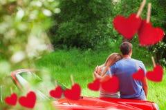 Sammansatt bild av att älska par som beundrar naturen, medan luta på deras cabriolet Royaltyfria Foton