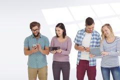 Sammansatt bild av att le affärsfolk som använder elektroniska grejer Fotografering för Bildbyråer