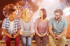 Sammansatt bild av att le affärsfolk som rymmer elektroniska grejer, medan sitta på skrivbordet Royaltyfri Fotografi