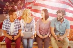 Sammansatt bild av att le affärsfolk som rymmer elektroniska grejer, medan sitta på skrivbordet Royaltyfria Foton
