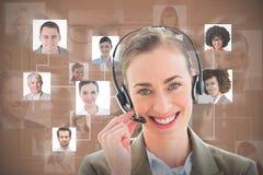 Sammansatt bild av att le affärskvinnan med hörlurar med mikrofon som ser kameran royaltyfri fotografi