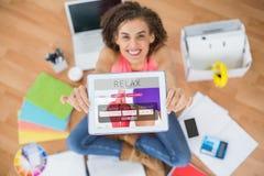Sammansatt bild av att le affärskvinnan som visar den digitala minnestavlan i idérikt kontor Royaltyfri Fotografi