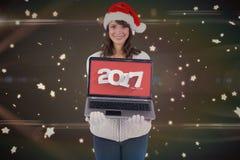 Sammansatt bild av att le brunett i den santa hatten som visar hennes bärbar dator Royaltyfri Foto