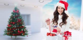Sammansatt bild av att le brunett i gåvor för santa hattemballage Arkivfoton
