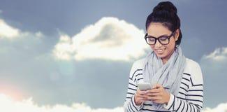 Sammansatt bild av att le den asiatiska kvinnan som använder smartphonen Royaltyfri Fotografi