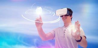 Sammansatt bild av att le den unga mannen som använder virtuell verklighetexponeringsglas arkivbilder