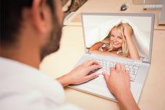 Sammansatt bild av att le kvinnan under ett duntäcke Royaltyfria Bilder