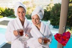 Sammansatt bild av att le kvinnor i badrockar som har te Royaltyfri Bild