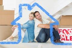 Sammansatt bild av att le par med askar i ett nytt hus Royaltyfri Fotografi
