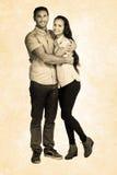 Sammansatt bild av att le par som kramar och ser kameran Royaltyfri Fotografi