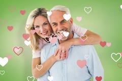 Sammansatt bild av att le par som omfamnar och ser kameran Royaltyfri Fotografi