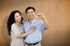 Sammansatt bild av att le par som rymmer en uppsättning av tangenter Arkivfoto