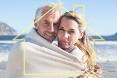 Sammansatt bild av att le par som slås in upp i filt på stranden Royaltyfria Foton