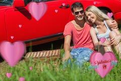 Sammansatt bild av att le parsammanträde på gräset som har picknicken tillsammans Royaltyfri Foto