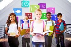 Sammansatt bild av att le små skolaungar i skolakorridor Royaltyfri Fotografi