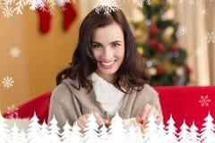 Sammansatt bild av brunetten som öppnar en gåva på soffan på jul Arkivbild