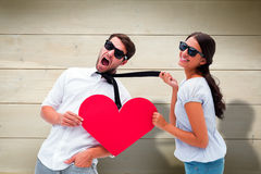 Sammansatt bild av brunetten som drar hennes pojkvän vid den hållande hjärtan för band Arkivbild