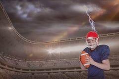 Sammansatt bild av den allvarliga amerikanska fotbollsspelaren som rymmer en boll Royaltyfria Bilder