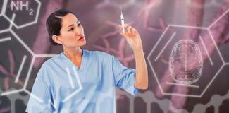 Sammansatt bild av den allvarliga doktorn som rymmer en injektion i sjukhus Royaltyfri Fotografi