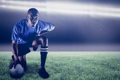 Sammansatt bild av den allvarliga rugbyspelaren som knäfaller medan hållande boll och 3d Royaltyfri Foto