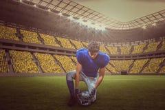Sammansatt bild av den amerikanska fotbollsspelaren som ner ser, medan rymma hjälmen med 3d Royaltyfria Foton