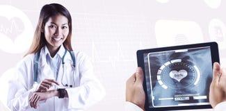 Sammansatt bild av den asiatiska doktorn som använder hennes smarta klocka Arkivbilder