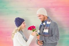 Sammansatt bild av den attraktiva mannen i erbjudande rosor för vintermode till flickvännen Arkivbilder