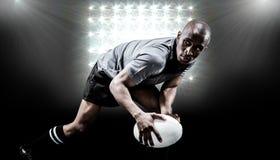 Sammansatt bild av den beslutsamma idrottsmannen som ser bort, medan spela rugby Royaltyfri Foto