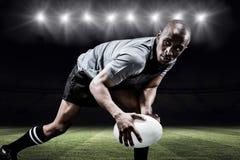 Sammansatt bild av den beslutsamma idrottsmannen som ser bort, medan spela rugby Arkivbild