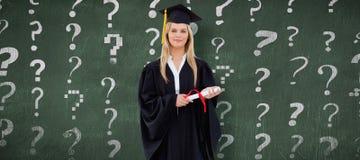 Sammansatt bild av den blonda studenten i den doktorand- ämbetsdräkten som rymmer hennes diplom Arkivfoto