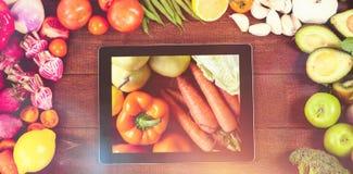 Sammansatt bild av den digitala minnestavlan som omges med nya grönsaker Royaltyfri Bild
