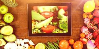 Sammansatt bild av den digitala minnestavlan som omges med nya grönsaker Arkivbild