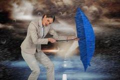 Sammansatt bild av den fulla längden av affärskvinnan som kämpar med det blåa paraplyet royaltyfria foton