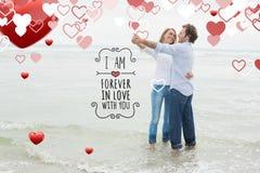 Sammansatt bild av den fulla längden av en pardans på stranden Arkivbilder