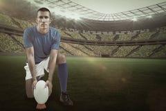 Sammansatt bild av den fulla längdståenden av rugbyspelaren som förlägger bollen med 3d Royaltyfri Bild