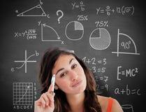Sammansatt bild av den fundersamma studenten som gör hennes läxa Royaltyfri Foto