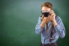 Sammansatt bild av den geeky hipsteren som rymmer en retro kamera Royaltyfri Foto